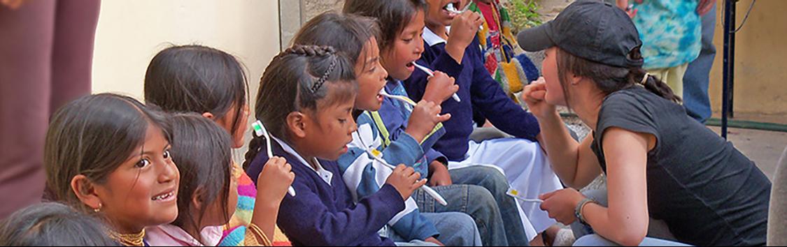 a volunteer is teaching children how to brush teeth